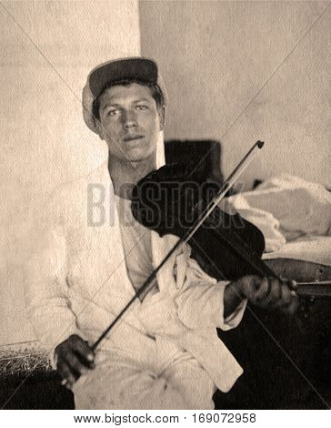 Vintage portrait of a young man with a violin,1927 year.