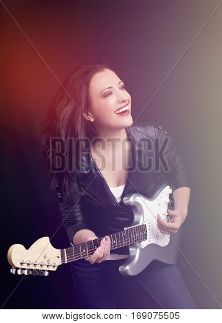 Beautiful girl with long hair playing guitar in rock style on a black background