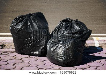 Piles of Black trash bags on the street