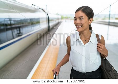 Happy Asian traveler smiling going on train travel in business class. Beautiful woman with hand luggage leaving on luxury transport. Businesswoman commuting to work in the morning. poster
