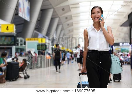 Businesswoman on commute transit talking on the smartphone while walking with hand luggage in train station or airpot going to boarding gate. Asian woman happy using mobile phone app for conversation.