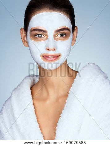 Smiling woman with moisturizing facial mask. Photo of brunette woman wearing white bathrobe. Beauty & Skin care concept