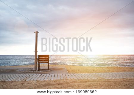 Landscape view on empty beach with chair next to street shower with fresh water in front of wavy sea and dramatic cloudy sky at sunrise with lens flare from sun light. Small path from wooden reeks behind