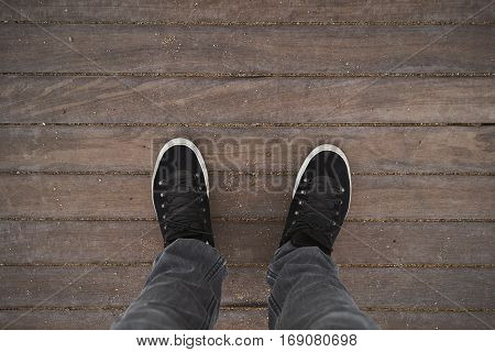 Top view on traveller legs stand on wooden reeks on empty beach, weared blank black sneakers and gray jeans