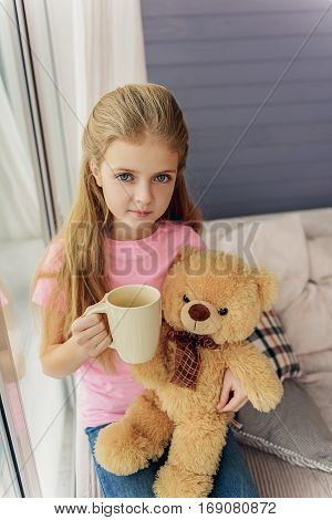 Carefree kid is playing with teddy bear at home. She is sitting on couch and holding cup. Girl is looking at camera with innocence