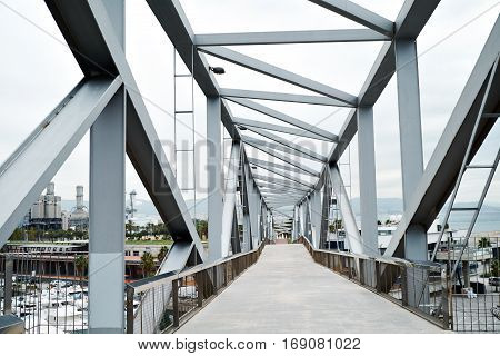 View on steel industrial bridge above sea port and big processing factory on background