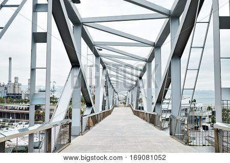 Walking industrial bridge with huge steel supports and geometrical shape above the yacht port is leading to processinc factory, landscape view