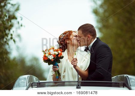 Happy Newlyweds Kiss Standing In The Car's Hatchway