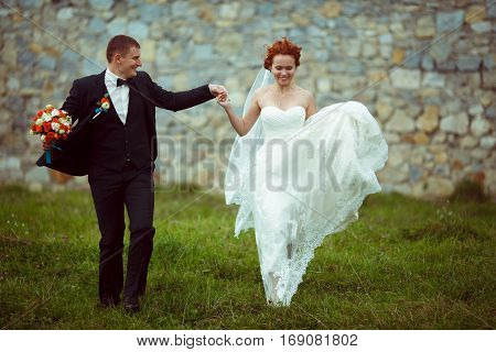 Bride and groom jumps up holding groom's hand