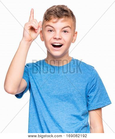 Cute teen boy pointing up, gesturing idea or doing number one gesture. Conceptual half-length emotional portrait of caucasian teen boy wearing blue t-shirt. Handsome child, isolated on white background.