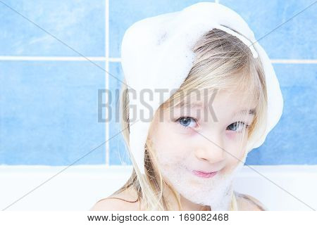 Adorable child blond girl with shampoo foam on hair taking bath. Closeup portrait of smiling kid, health care and hygiene concept.