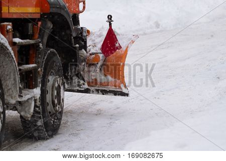 rear view of orange tractor with plough driving down snow on a city street in the middle of winter snowfall