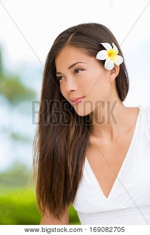 Asian mixed race beauty woman with healthy hair wearing hawaiian flower. Wellness skincare happy lifestyle. Serene multicultural girl outdoors at tropical spa. Young mixed race model on Hawaii.
