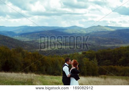 Happy Wedding Couple Kisses Standing In The Front Of A Great Mountain Landscape