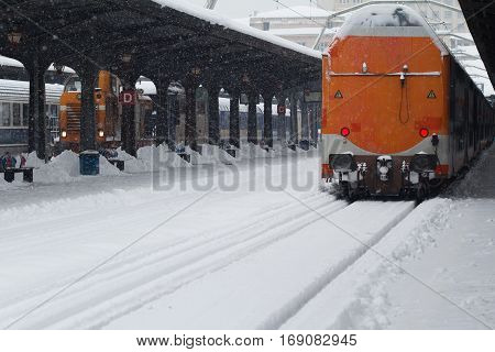 Rear view of the back of an orange passenger train covered in snow stopped in railway station winter time