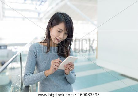 Woman using mobile phone in departure hall