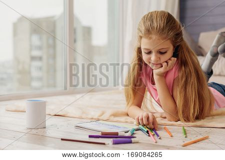 Pretty girl is drawing picture with inspiration. She is lying on floor at home