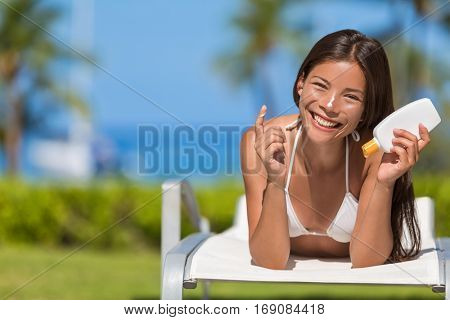 Suntan lotion woman applying sunscreen solar cream. Beautiful happy cute woman asian applying suntan cream from a plastic container to her nose with ocean in background.