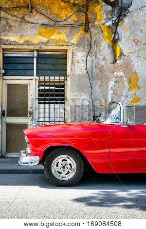 HAVANA,CUBA - JANUARY 7,2017 : Classic red convertible car next to a shabby building in Old Havana