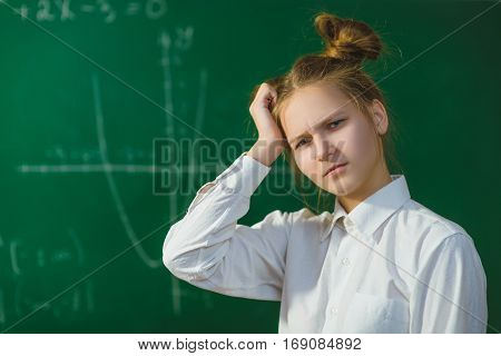 Girl thinking on blackboard background . Educational and school concept.