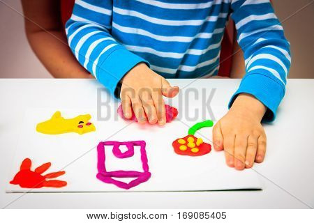Child playing with clay molding shapes, kids learning concept