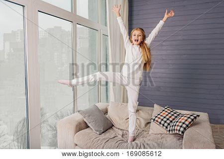 I am free. Cheerful girl is playing in living room. She is standing on sofa on one leg and stretching arms up. Kid is laughing