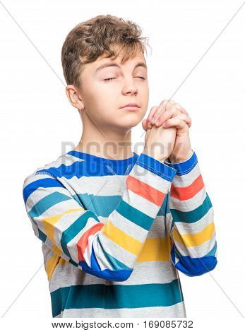 Portrait of caucasian teen boy closed his eyes and saying prayers. Handsome child praying and praising God, isolated on white background. Religious image - teenager hands clasped in prayer prays to God.