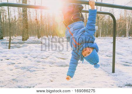 little boy playing on monkey bars in winter snow