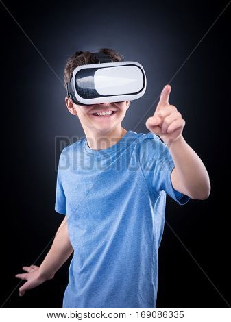 Happy teen boy wearing virtual reality goggles playing video games, on black background. Cheerful smiling looking in VR glasses and gesturing with his hand. Child experiencing 3D gadget technology.
