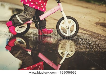little girl riding bike in water puddle, kids play water