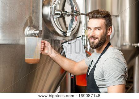 Brewer pouring beer wort from the metal container checking the quality at the brewery