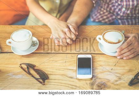 Young couple toasting coffee cappuccino at bar cafeteria shop - People holding each othres hands for tender love moments - Relationship concept - Focus on right man hand - Warm cinematic filter