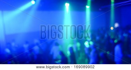 Blurred people dancing with original laser blue lights - View of new generation disco club - Defocused image - Concept of nightlife with music entertainment - Warm filter