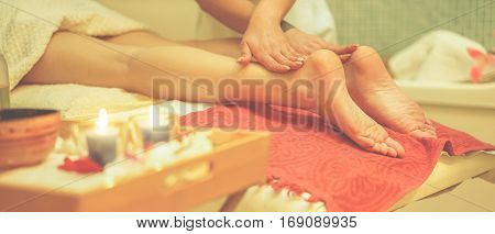 Young woman having feet therapy massage in spa resort hotel salon - Female enjoying relaxing treatment - Body care wellness and chilling concept - Focus on masseuse left hand - Warm cinematic filter