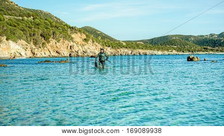 Young fisherman inside sea with speargun and fish in his hands - Man hunting near seashore in italian beach coast for sport hobby vacation - Holidays concept - Focus on him - Warm vivid filter