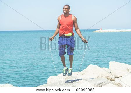 Afro american man jumping rope with sea view in background - Young african athlete training outdoor - Healthy lifestyle concept - Focus on his face - Warm cinematic filter