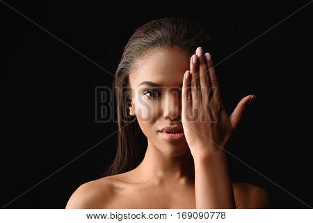 Beauty and perfection. Sensual young mulatto girl is covering her eye by hand. She is standing with naked shoulders. Isolated on black background