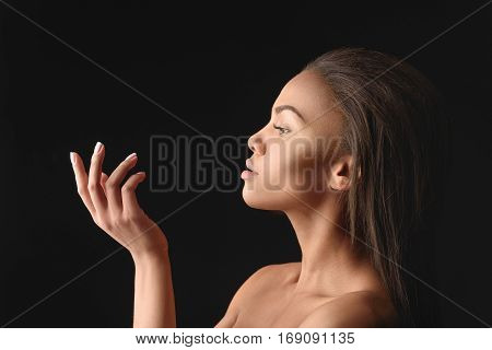 I have perfect smooth skin. Voluptuous young african woman is looking at her hand with satisfaction. Isolated on black background