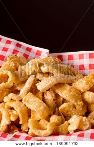 Delicious crispy pork rinds. A crisp salty snack on black glossy background