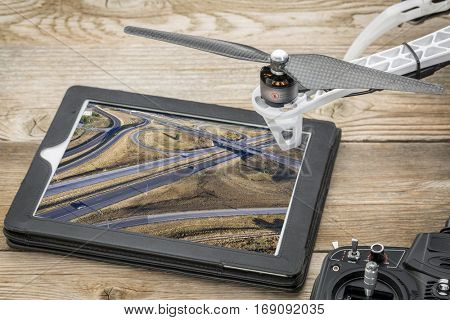 aerial landscape photography concept - reviewing aerial pictures of a freeway in Colorado on a digital tablet with a drone rotor, screen picture copyright by the photographer