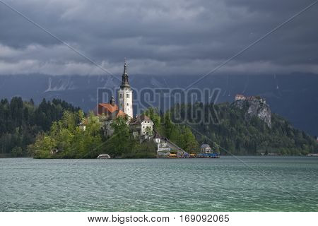 Island on Bled lake and pilgrimage church of the Assumption of Mary in sunlit with mountain covered dark clouds on background , Slovenia