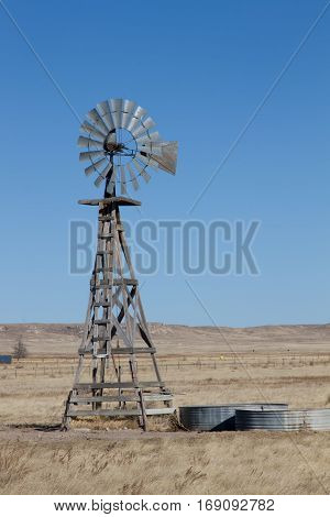 An agriculture farming windmill on the eastern plains of Colorado with the hills of the Pawnee Buttes Grasslands in the background