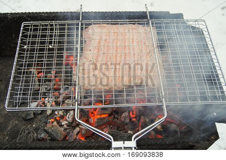 Meat being prepared on the coals with smoke. Cooking meat on the coals in the open air.