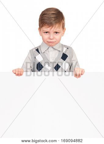 Portrait of a unhappy little boy with blank signboard, isolated on white background. Sad child holding banner and looking at camera. Funny kid peeking from behind empty panel or placard board.