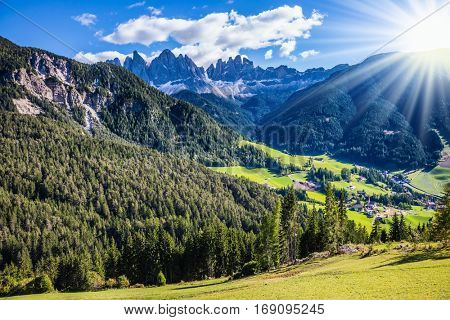 The concept of eco-tourism in Alpine meadows. The sun illuminates rural farm and green alpine valley in the Dolomites. Beautiful autumn day
