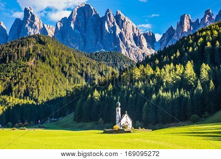 The symbol of the valley Val di Funes - church of Santa Maddalena. Rocky peaks and forested mountains surrounded by green Alpine meadows. Tirol, Dolomites. Sunny warm autumn day