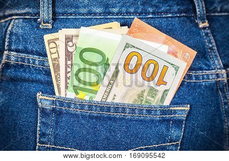 Different banknotes of Euro and american currency sticking out of the back jeans pocket. Money in jeans pocket for travel and shopping