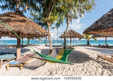 handmade wooden chaise longues, straw umbrellas and hammock on a beach near ocean