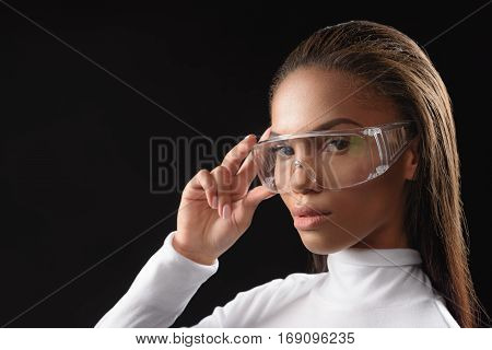 Smart young african woman is standing and touching her eyewear with assurance. Isolated and copy space in left side