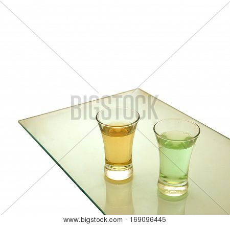 Two glass shots on table isolated on white